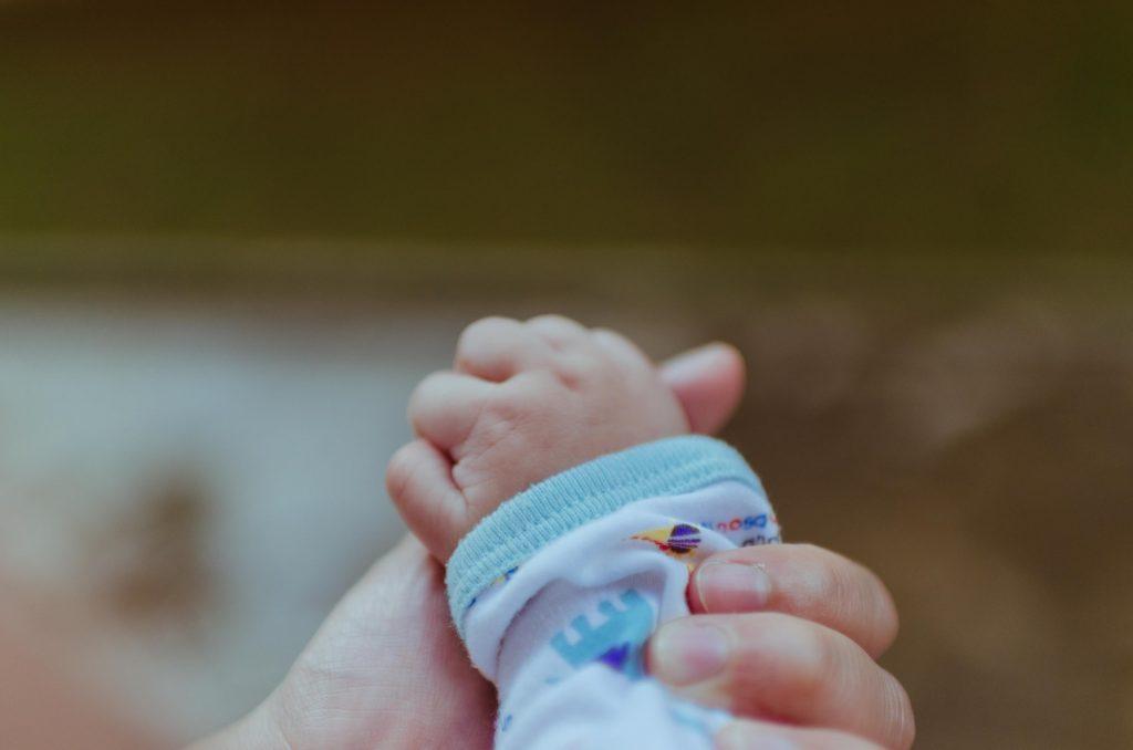 Mamă își ține de mână bebelușul